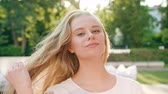 чувственный : A happy smiling blonde woman straightening her hair in the city street. Close-up shot. Soft focus