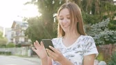 модель : An attractive young lady using a phone in town. Close-up shot. Soft focus