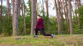 egzersiz : A young man stretching in the forest. Long shot Stok Video