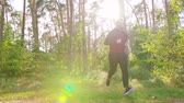 coureur : A young man running in the forest. Long shot. Lens flare