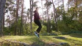 coureur : A young man jumping in the forest. Long shot