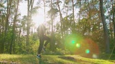 egzersiz : A young man jumping in the forest. Long shot. Lens flare Stok Video