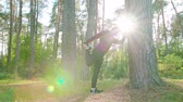coureur : A young man stretching in the forest leaning against a tree. Long shot Vidéos Libres De Droits