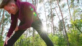 coureur : A young man stretching in the forest. Long shot. Lens flare