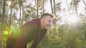 coureur : A young man stretching in the forest. Medium shot. Lens flare Vidéos Libres De Droits