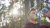 coureur : A young man drinking water in the forest. Clos-up shot. Lense flare