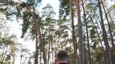 запустить : A young man walking in the forest. Clos-up shot. Lense flare