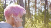 coureur : A young y with pink hair walking in the forest and listening to music. Close-up shot Vidéos Libres De Droits