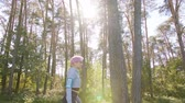 coureur : A young y with pink hair walking in the forest and listening to music. Medium shot