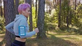 coureur : A young women with pink hair jogging in the forest. Medium shot Vidéos Libres De Droits