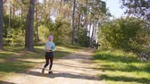maratona : A young y with pink hair jogging in the forest. Long shot Stock Footage