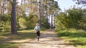 coureur : A young y with pink hair jogging in the forest. Long shot Vidéos Libres De Droits
