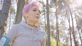 coureur : A young y with pink hair takes a break after jogging in the forest. Medium shot Vidéos Libres De Droits