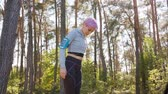 coureur : A young y with pink hair stretching in the forest. Long shot Vidéos Libres De Droits