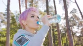郊外の : A young y with pink hair drinks water after jogging in the forest. Medium shot
