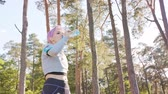 郊外の : A young women with pink hair drinks water after jogging in the forest. Medium shot 動画素材