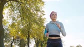 coureur : A young y with pink hair jogging in the forest. Medium shot Vidéos Libres De Droits