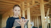 cantiere edile : A young lady using a tablet in a house under construction. Long shot. Soft focus. Close-up shot Filmati Stock