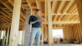 cantiere edile : A young lady using a tablet in a house under construction. Long shot. Soft focus. Medium shot