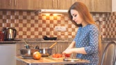 handheld : Healthy food lifestyle: beautiful woman casually cooking, cutting vegetables at kitchen. Medium shot, handheld, slow motion 60 fps.