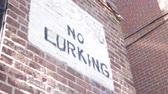střední : Low angle of No Lurking sign painted on brick wall