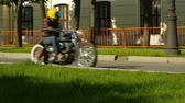 motorcyclist in a leather jacket and helmet rides on a chopper along the street, slow motion Stock Footage