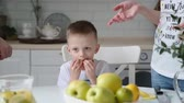 drooling : little boys and girls eat in the kitchen Apple
