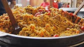 plov : Cooking pilaf in a cauldron. Rice with meat and vegetables. Asian traditional dish - pilaf. National tasty food. Close up. Steamed food. Stock Footage