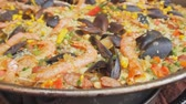 rice pan : Spanish paella with yellow rice, shrimps and mussels cooking at the food market.