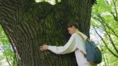 sentido : Girl hugs the big tree in the forest, love for nature.