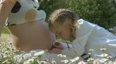 olasılık : Cute little girl with stethoscope play doctor with pregnant mother. A girl with pigtails examines mothers belly. Happy Mother and Daughter having fun outdoors and enjoying nature together.