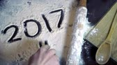vinte anos : Numbers 2017 written on white flour. Preparing for new year. New year concept. Holiday baking. New year background. Finger writting 2017 on flour. Holiday concept. New 2017