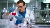 проведение : Scientist in lab. Scientist looking at chemical liquid in research laboratory. Scientist working in laboratory with chemical reagents. Lab man carrying out scientific research in lab. Scientist lab