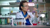 analyzing : Female chemist in laboratory. Chemist analyzing chemical liquid in test tube. Woman chemist conducting chemical research in chemistry lab. Chemist woman working with chemical reagents in lab flask