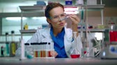 проведение : Woman researcher in lab. Research scientist working in research laboratory. Female researcher analyzing chemical liquid in laboratory glassware. Laboratory research concept. Researcher in laboratory