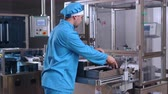 farmacêutico : Factory operator control pharmaceutical packaging machine. Pharmaceutical manufacturing process. Pharmaceutical worker take packaging from manufacturing line. Pharmaceutical factory. Pharmacy factory
