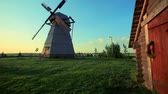 солнечные лучи : Rural house on village landscape. Windmill farm on background sunlight. Panoramic view of country house and windmill. Wooden house and windmill in rural yard. Beautiful view village nature