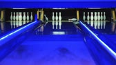bodování : Playing bowling game on colorful alley. Bowling ball knocks down 7 pins. Process of bowling game. Bowling strike competition. Colorful Illumination. Ball is rolling on playing field
