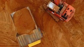 dumper : Sand work aerial view. Drone view of mining truck and excavator working at sand quarry. Mining excavator pouring sand in dump truck. Aerial view of mining equipment. Mining machinery at sand mine Stock Footage