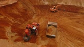 dumper : Aerial view of mining machinery working at sand quarry. Mining excavator pour sand in sand truck. Sky view of mining equipment on sand mine. Mining machines working in sandpit. Construction industry Stock Footage