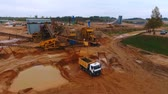 madencilik : Sand extraction at quarry. Sky view of mining equipment working at industrial area. Mining truck moving at industrial territory sand mine. Mining conveyor pour sand at dumper truck. Aerial view Stok Video