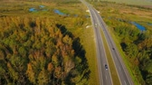 příjezdová cesta : Highway road in forest landscape. Aerial view of cars driving on asphalt road between trees. Drone view of highway in forest. Cars moving on country road. Highway road in forest. View from above Dostupné videozáznamy