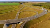enrolamento : Aerial highway. Highway junction. Winding road. Top view cars driving on road junction. Cars traffic at highway junction aerial. Aerial view road intersection in field. Highway road