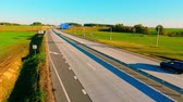 маршрут : Cars and cargo trucks driving on highway road. Highway sing on country road. Cars traffic on country road. Cars moving on road aerial view. Drone view of highway traffic