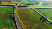 freeway interchange : Aerial view cars moving on highway intersection in green fields. Aerial landscape road junction. Aerial highway road top view. Aerial highway crossing in nature landscape. Crossing road sky view Stock Footage