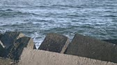 hasarlı : Concrete breakwaters. Water splash on pier rock. Splash of water about concrete blocks on seashore. Waves splashing on rocky coast. Sea waves crashing on beach rock