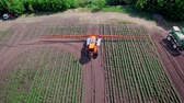 farming equipment : Agricultural sprayer fertilizing plant on farming field. Sky view process watering agricultural field using spraying machine. Agriculture industry. Fertilizer spreader. Agriculture irrigation machine