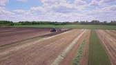 arando : Agricultural tractor with trailer working on farming field. Drone view farming tractor driving on plowed field. Farming machinery on agricultural field. Agricultural machinery. Farming aerial