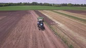arando : Agricultural tractor with trailer for plowing working on arable field. Aerial view farming tractor driving on plowed field. Farming equipment on field. Agricultural industry. Agriculture machine work