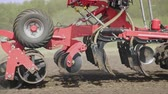 farming equipment : Agricultural machinery scattering seeds on farming field. Close up sowing machine working in rural field